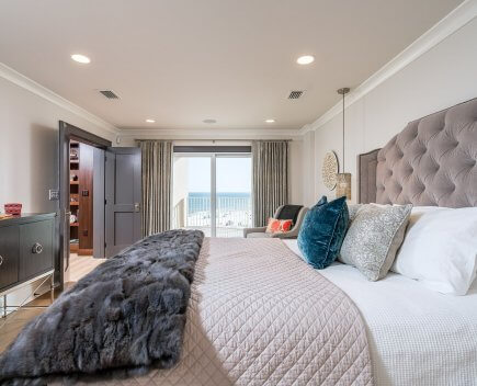 Condo Master bedroom with tufted upholstered bed, custom throw pillows, hanging lights and accent chair.