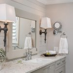 Coastal bath, countertop and sink with polished nickel faucet and wooden oval mirror with silve studs crystal cabinet pulls, large mirror and beautiful sconces in Pensacola Florida