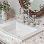 Coastal bath, countertop and sink with polished nickel faucet and wooden oval mirror with silve studs crystal cabinet pulls in Pensacola Florida
