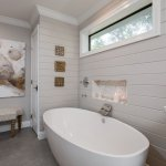 large freestanding tub with waterfall faucet neutral walls and grey tiles flooring