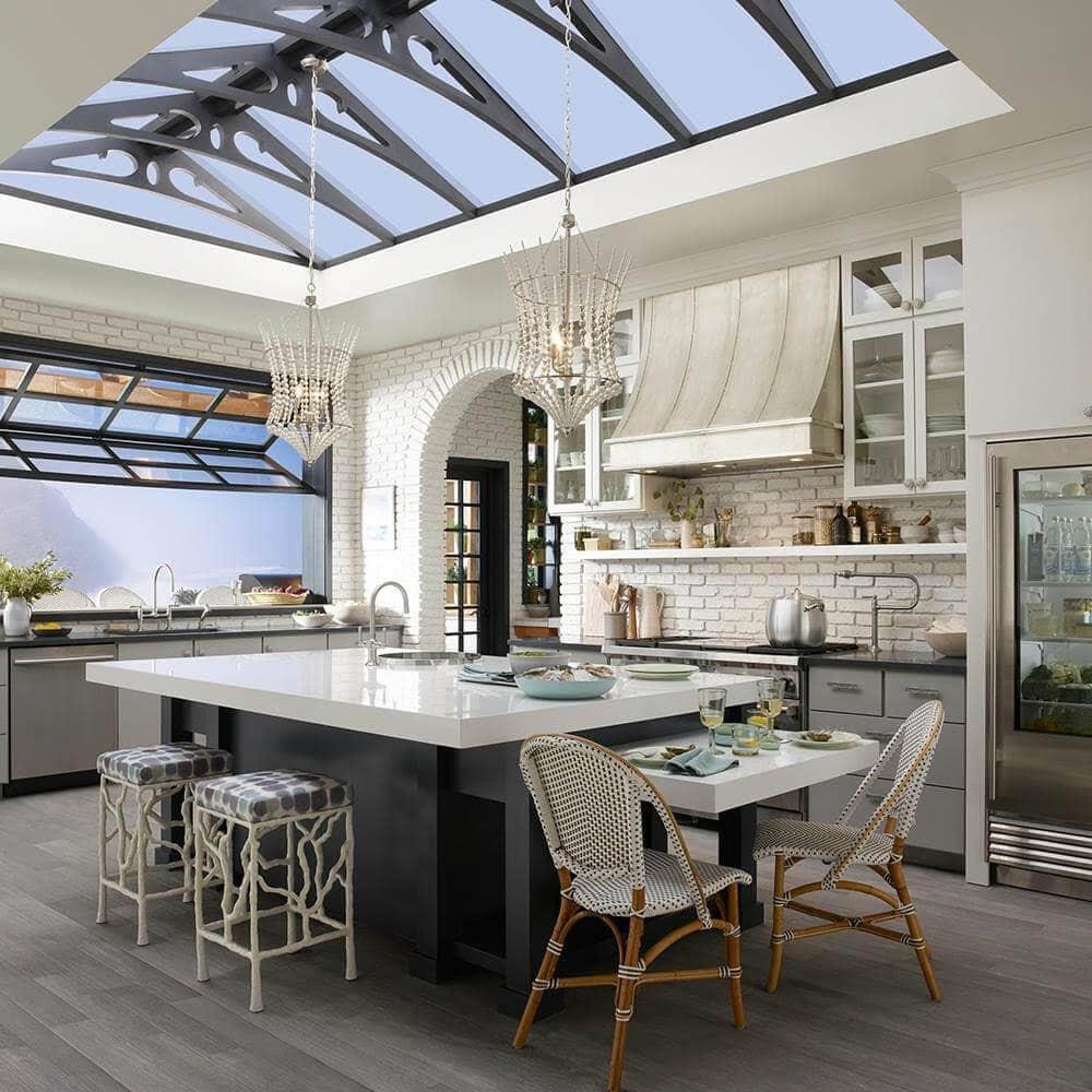 garden kitchen with vaulted ceiling kitchen island beautiful wood flooring white beaded hanging lights, garage style window, custom counterstools,
