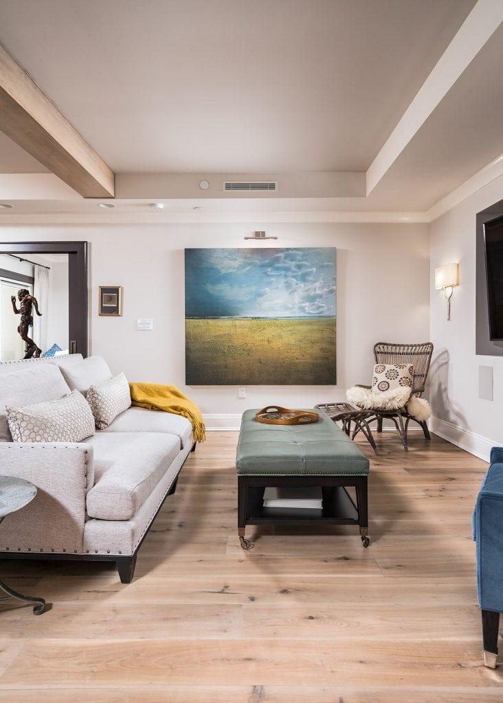 Penthouse suite turned family home with open living room with light hardwood flooring original art linen sofa blue velvet chair art