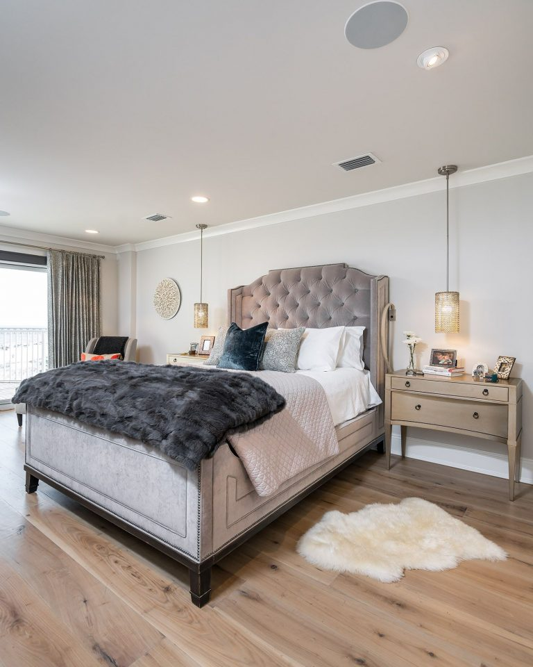 light, airy bedroom design with light hardwood flooring, velvet upholstered bed, wood console with metal base