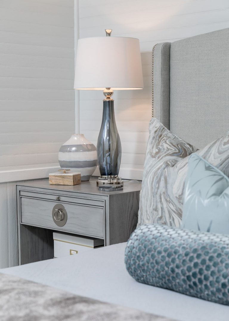 nutral bedroom with smoket grey glass lamp upholstered bed with grey side table