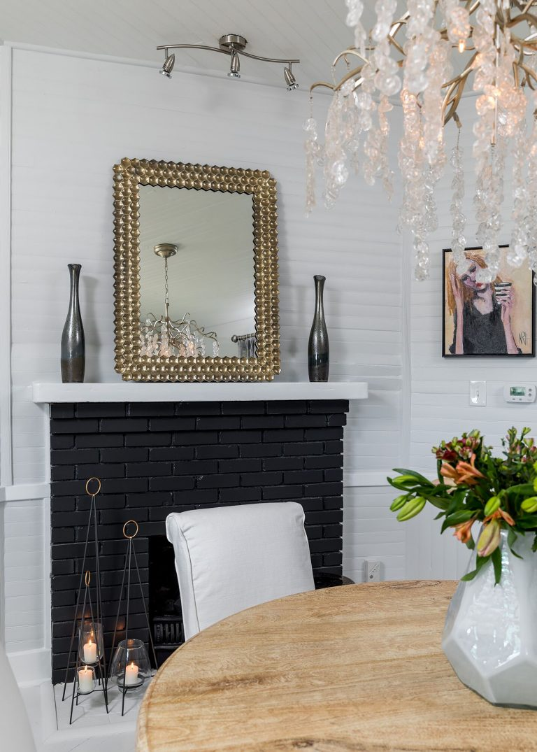 white cottage design black brick painted fireplace with gold frame mirror