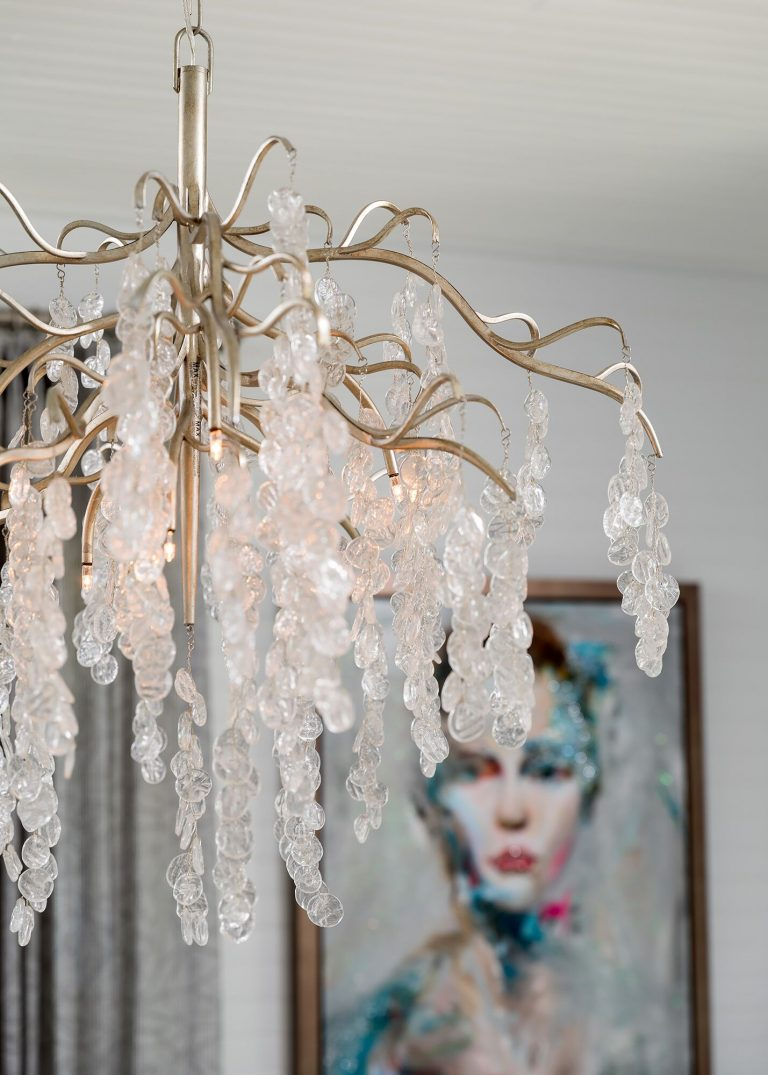 gold and clear crystal hanging light with colorful portrait painting in background