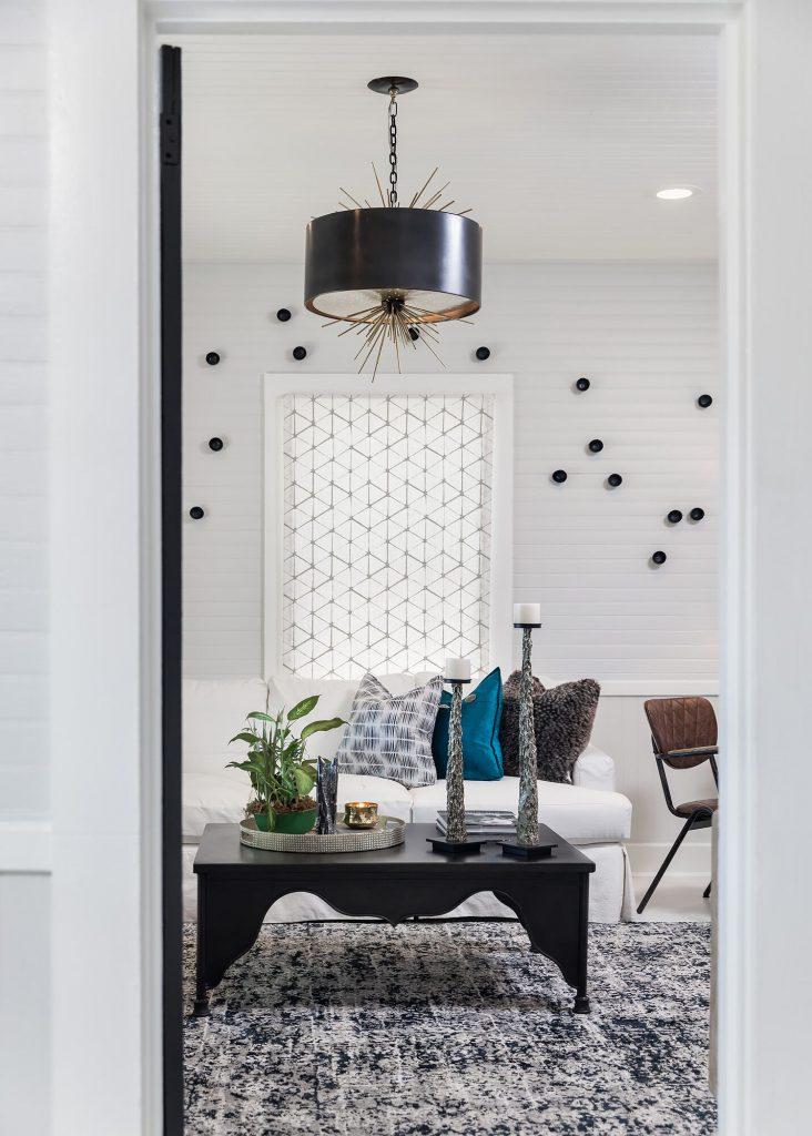 white cottage with black & white rug black lacquer coffee table white slipcover sofa black hangin light with gold startburst