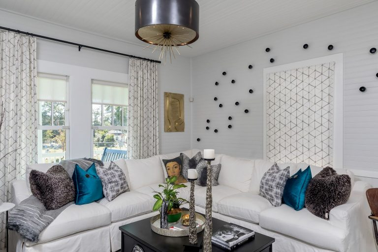 white cottage with black hanging light with gold starburst white slipcover sofa black lacquer coffee table