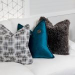 white sofa with black & white pillow teal blue pillow and grey fluffy pillow