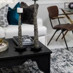black alcquer coffee table metal candlesticks white sofa black & white rug wooden desk chair