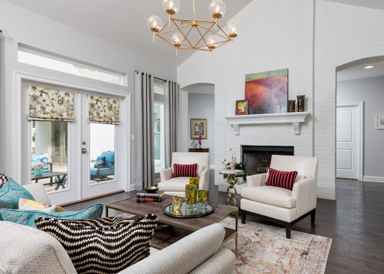 white brick living room with gold chandelier colorful art painting white upholstered chairs dark hardwood flooring, vintage style rug