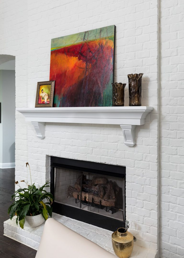 white brick fireplace with plant, colorful painting