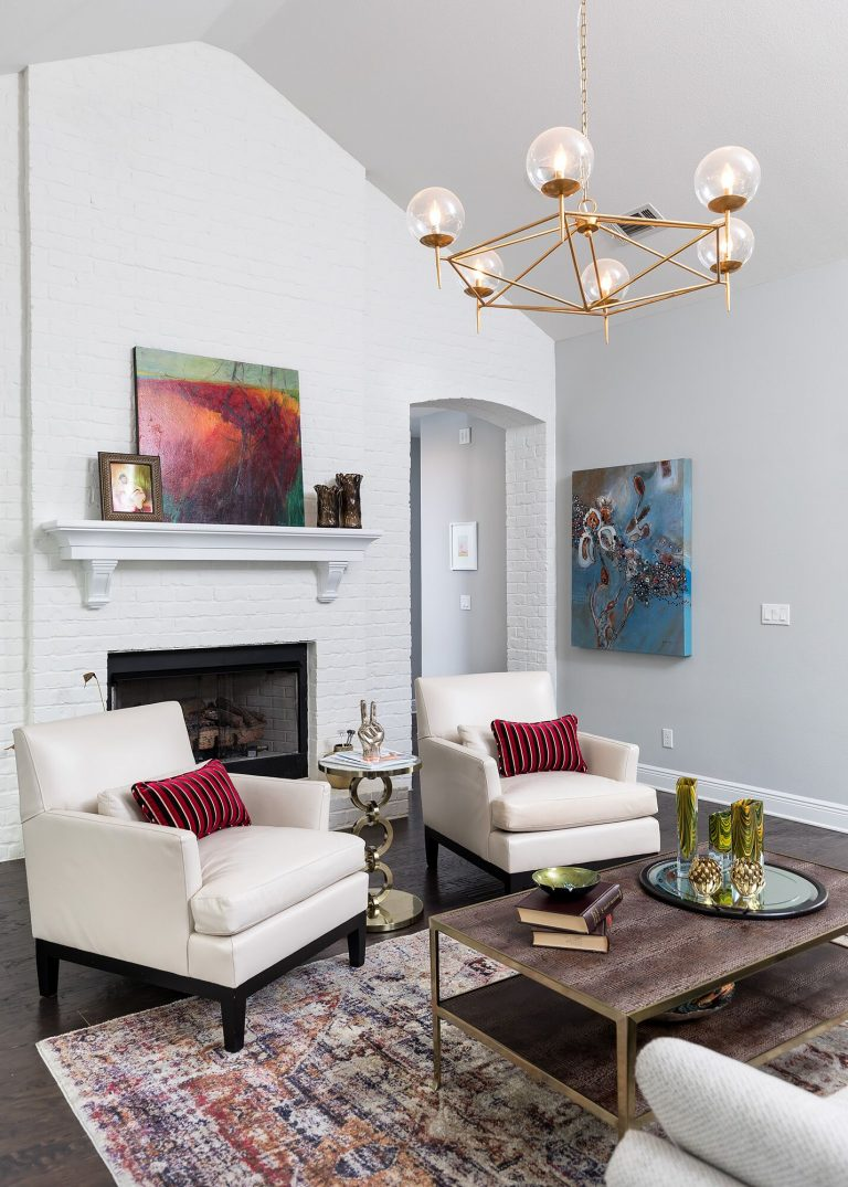 white brick living room with gold hanging light blue green and red painting white upholstered chairs dark hardwood flooring, vintage style rug