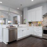 open concept kitchen and living room silver pendant lights neutral tile backsplash
