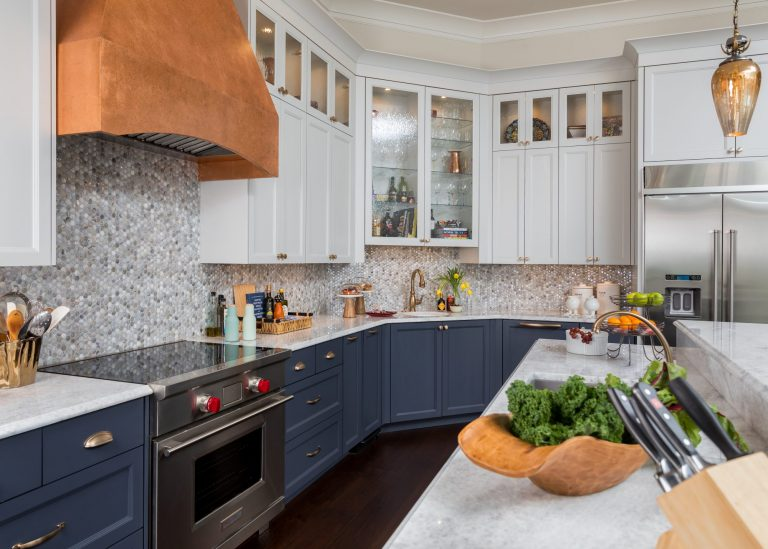 Blue bottom cabinets with brass pulls and marble countertops. White upper cabinets with brass knobs. Cabinets with glass fronts and lighting. Mosaic tile backsplash and faux copper finish on hood vent and pendant.