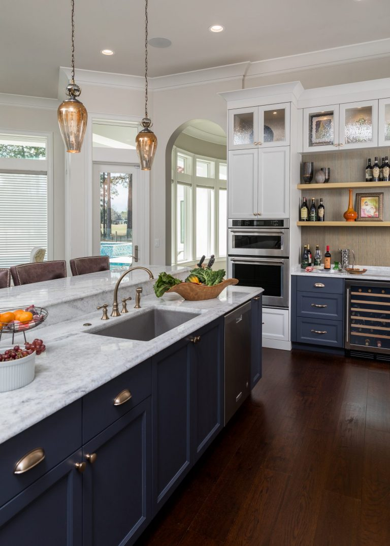 Blue bottom cabinets with brass pulls and marble countertops. White upper cabinets with brass knobs, glass fronts, and lighting. Dark hardwood floors, crown molding and hanging lights.