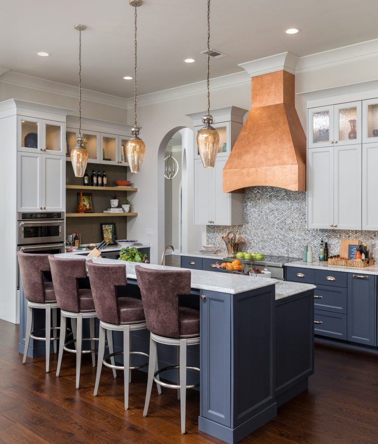 Destin Florida kitchen design with copper hood. Blue bottom cabinets and island with brass hardware. White upper cabinets with brass knobs, glass fronts, and lighting. Mosaic tile backsplash, hardwood floors, and crown molding. Custom Bar stools.