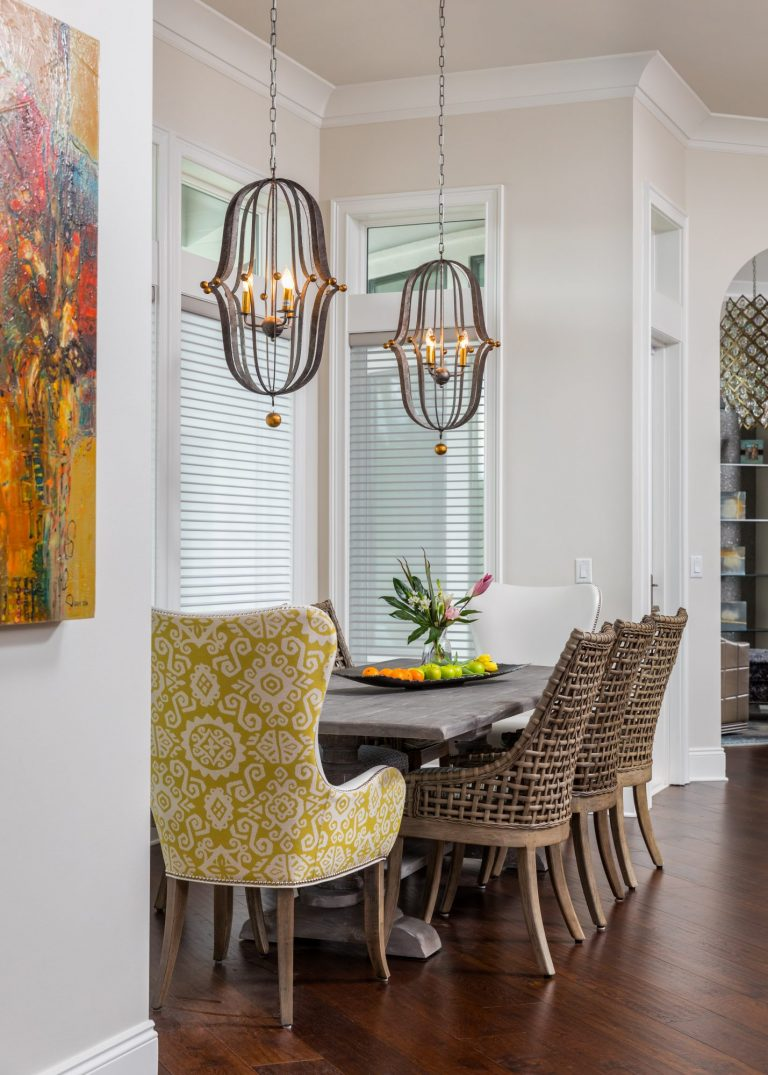 Breakfast area designed with original art, hanging lights, and custom dining chairs.