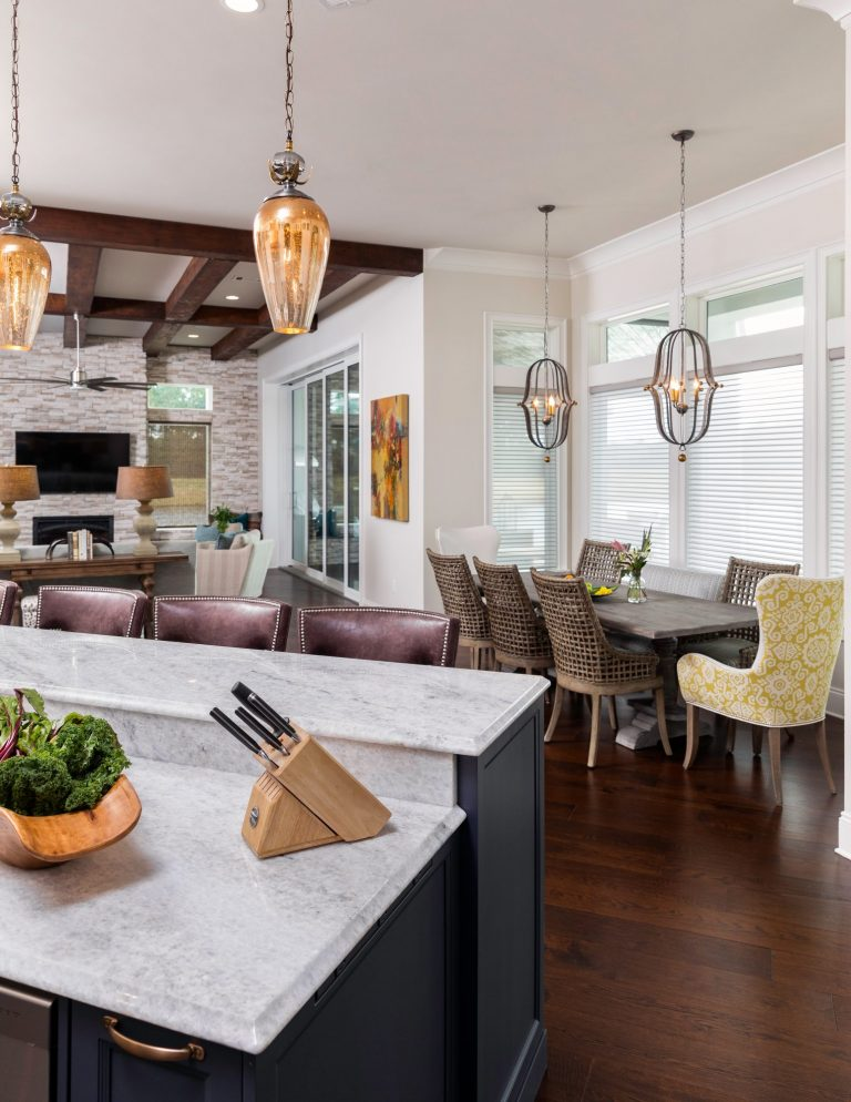 Family friendly kitchen design with blue island and marble countertops, hanging lights and original art. Breakfast area with hanging lights and custom dining chairs.