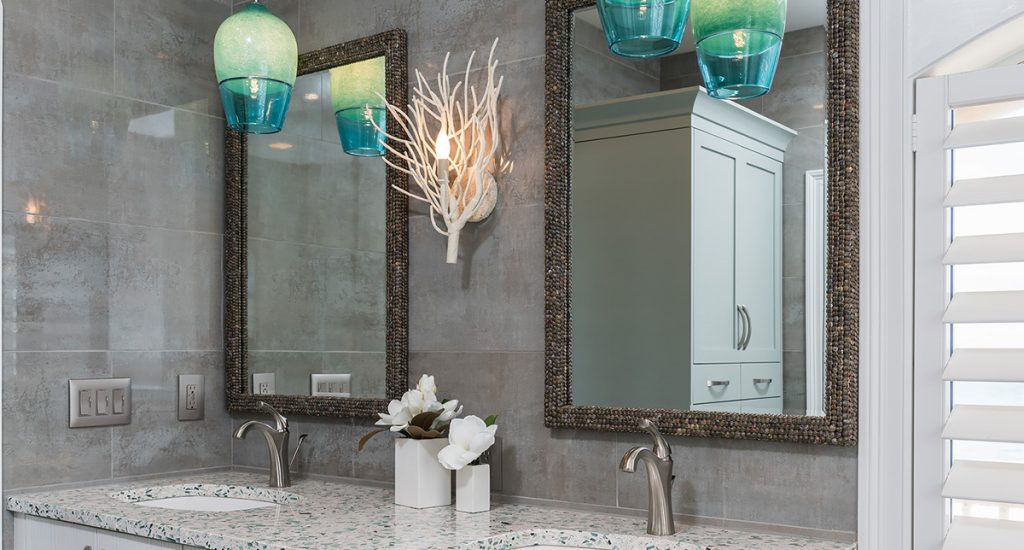 Grey tiled walls with white vanity and quartz countertops. Coral Sconce with two mirrors and two aqua pendants.
