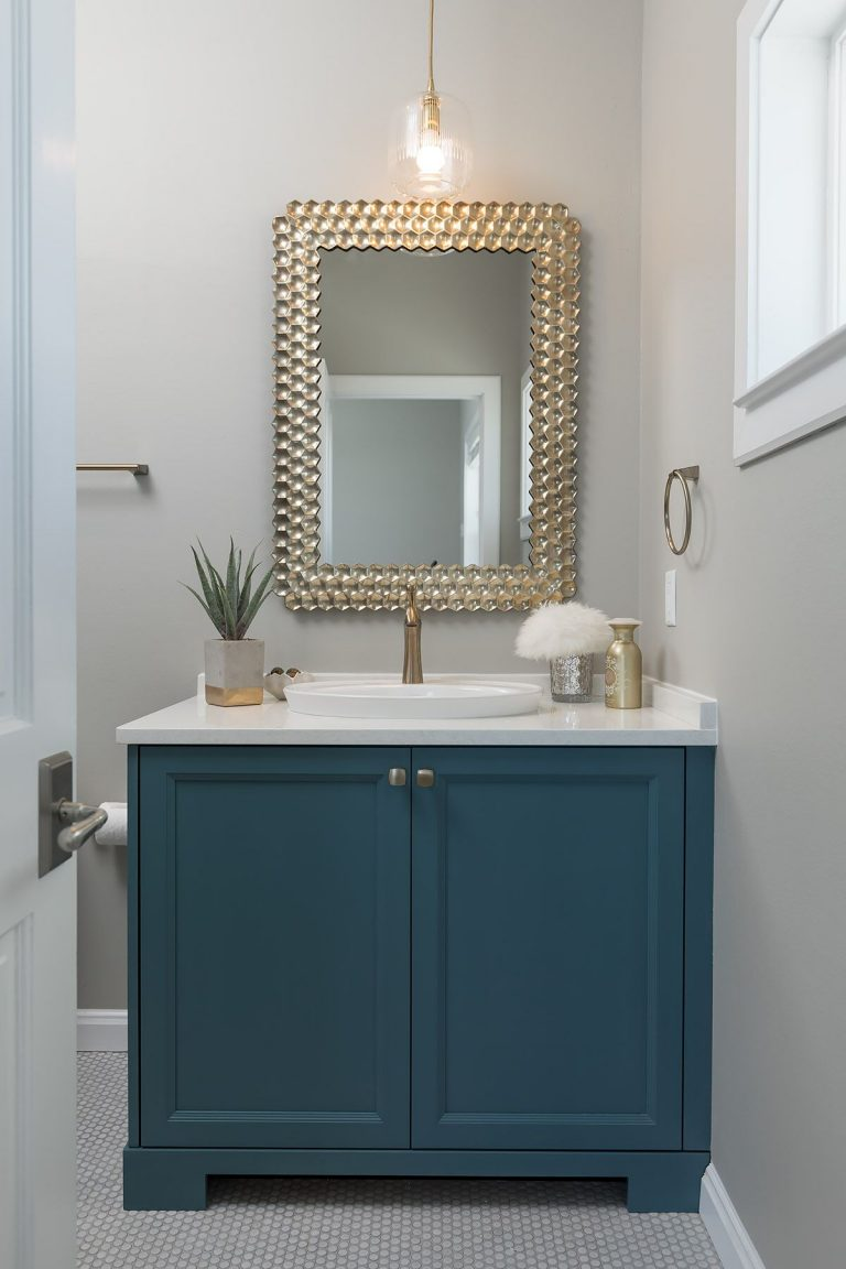 round penny floor tile, blue bathroom cabinet, white countertop, and accent mirror