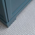 round penny floor tile and blue cabinet