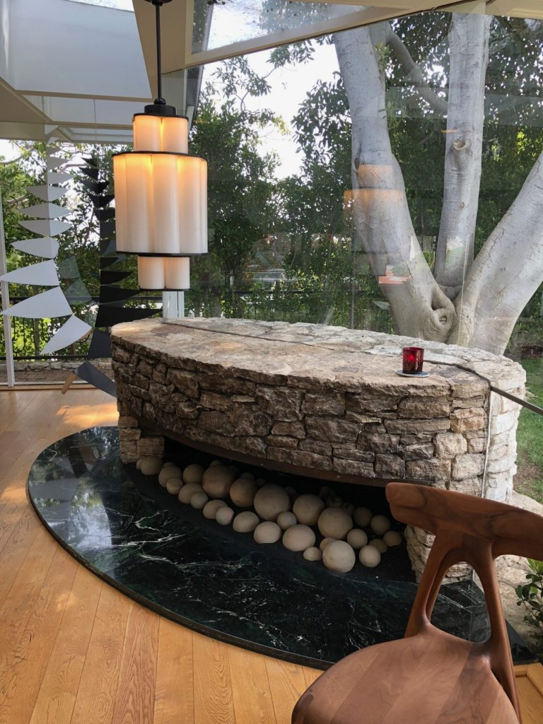 stone fireplace encased in glass wall