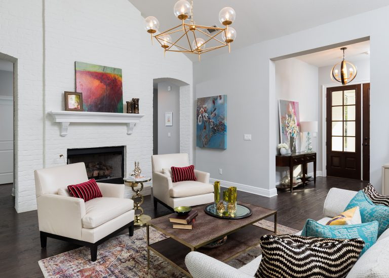 Modern sofa with vibrant custom throw pillows. Cream colored accent chairs in front of a painted white brick wall with fireplace. Original art, vintage style rug and gold chandelier