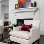 Cream colored accent chairs in front of a painted white brick wall with fireplace. Original art and vintage style rug