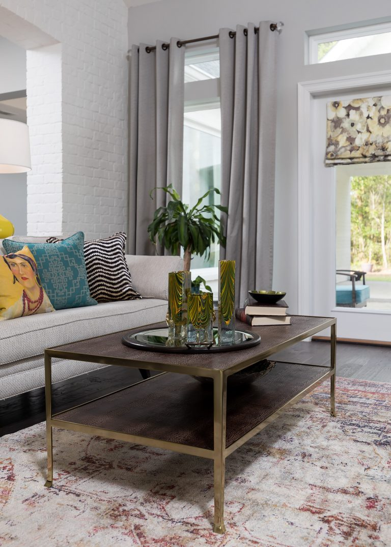 white brick living room with cute sofa colorful pillows, neutral curtains, wood coffee table, vintage style rug