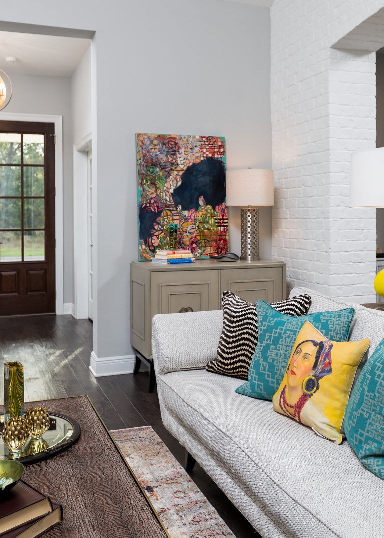 black door, white brick living room with cute sofa colorful pillows, colorful art