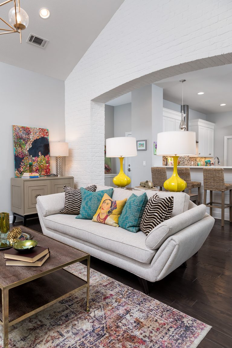 white brick living room with cute sofa colorful pillows, gold chandelier