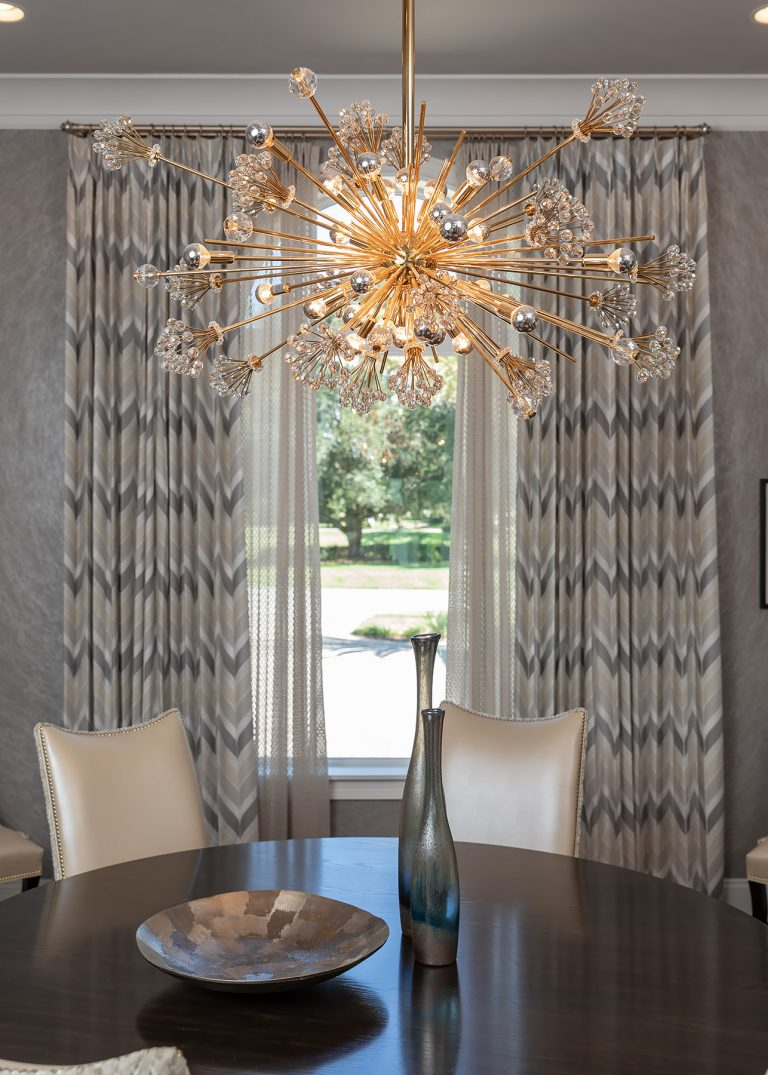 Grey drapes with chandelier and dining table