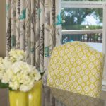 Green dining chair with green home decor and colorful curtains