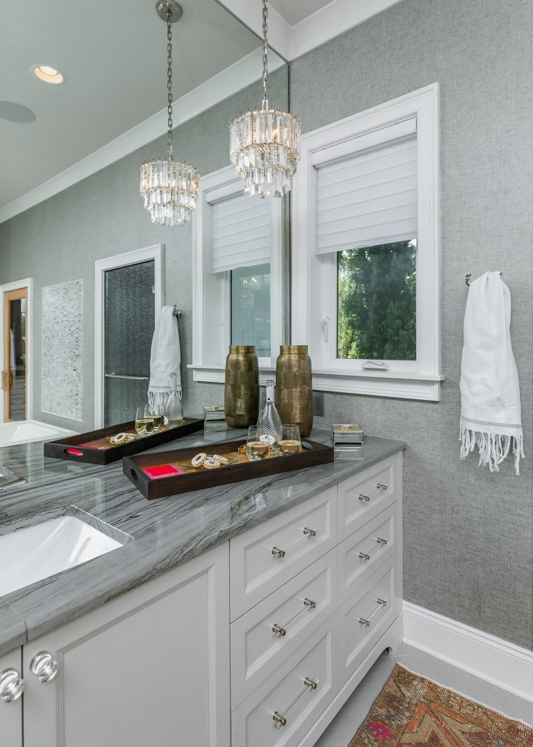 Master Bathroom Sink with grey wallpaper and cabinets
