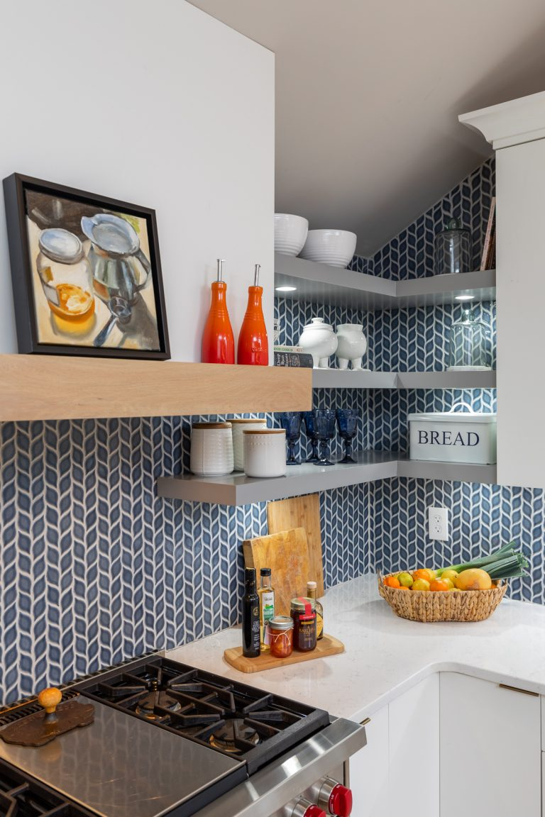Blue Kitchen Back splash with grey floating shelves and white counter tops with white cabinets