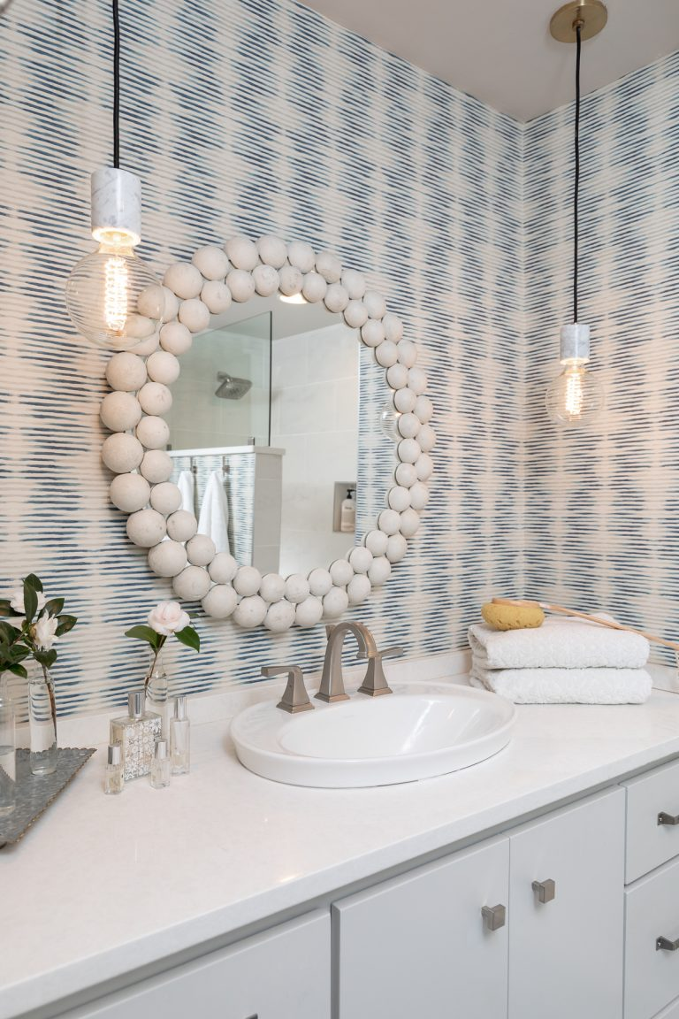 White and Blue Bathroom with wallpaper and white mirror - glass modern pendants - white counter tops with grey cabinets - Scandinavian design