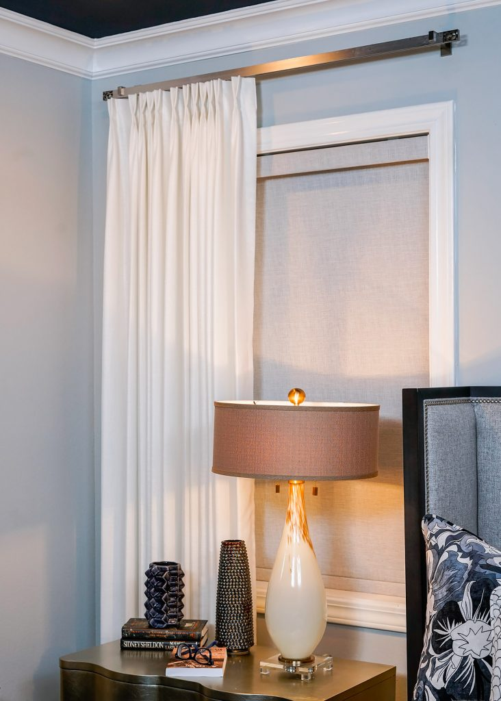 window curtains on one side of a window bed in middle