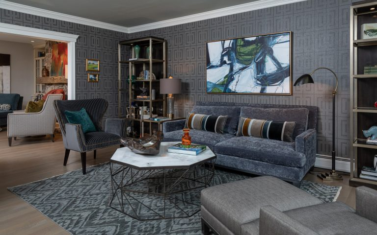Colonial Living Room Makeover, New Jersey - Grasscloth wallpaper, bookcase, grey accent chair, original art, stone top coffee table and dark furniture; bold color
