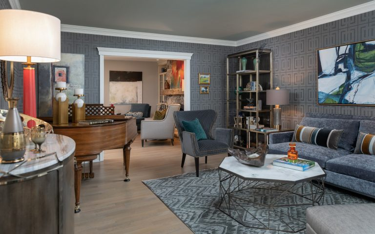 Colonial Living Room Makeover, New Jersey - Grasscloth wallpaper, bookcase, grey accent chair, original art, stone top coffee table and dark furniture