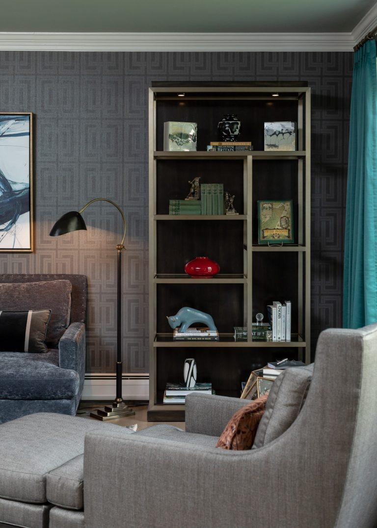 Colonial Living Room Makeover, New Jersey - Grasscloth wallpaper, bookcase, grey accent chair, original art, black and gold floor lamp, and dark furniture