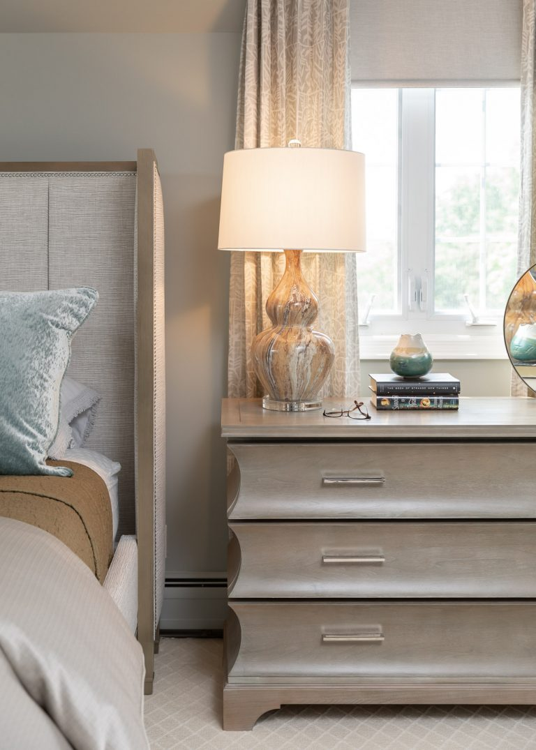 neutral colored bedding, light and airy master bedroom, light wood night stand, accent lamp