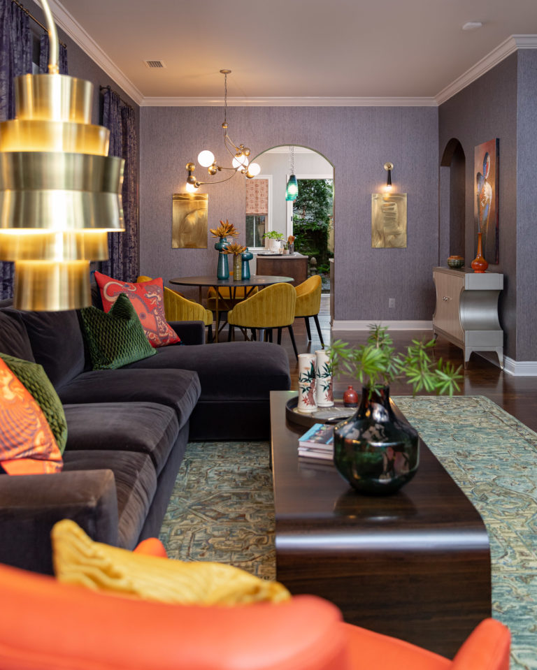 colorful, rich , moody living room , living room ideas, colorful living room, purple velvet sofa, red leather chairs, green area rug, nancy rhodes harper art, gold floor lamp