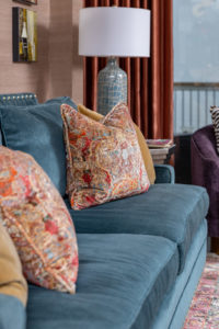Blue sofa with nailheads and accent pillows - coastal condo remodel pensacola beach florida