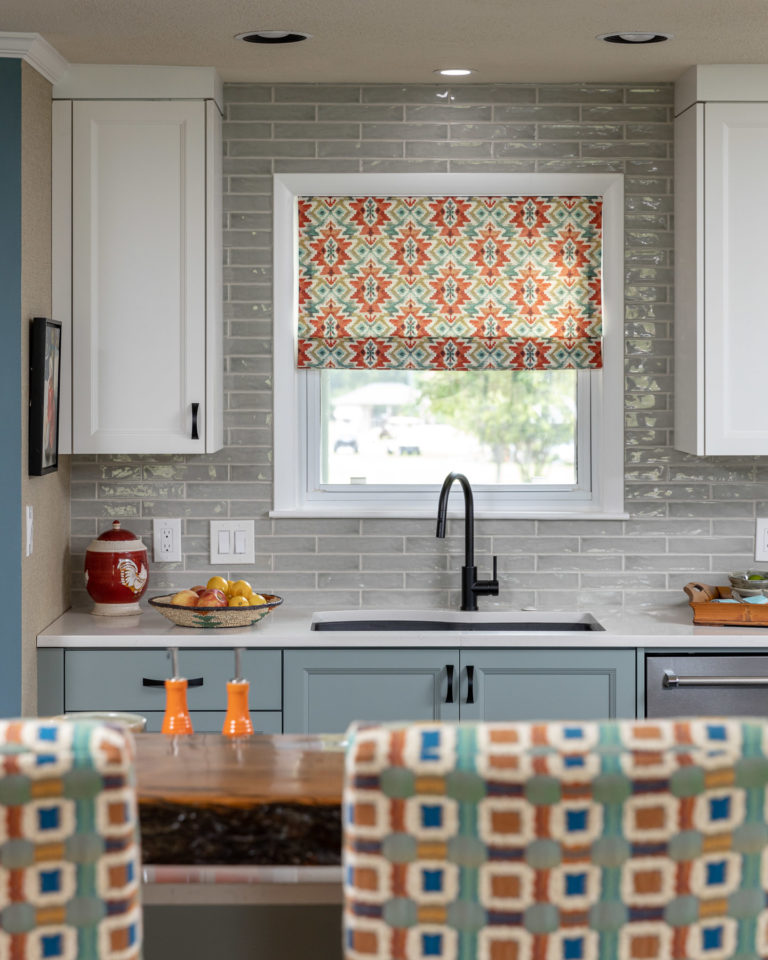 blue cabinets, grey backsplash, wood bar top, white cabinets, black cabinet hardware, barstool, window treatment