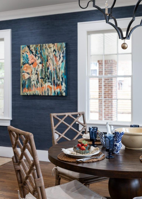 Original local art, navy blue textured wallpaper, dining room table