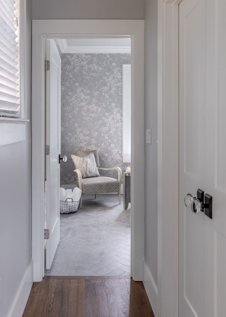 entry way to master bath with grey paint and floral wallpaper with grey velvet accent chair