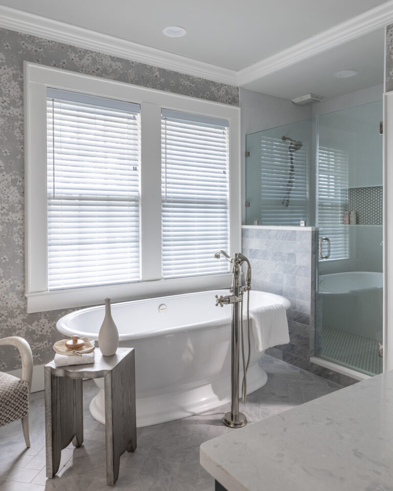 walk in grey tiled shower with glass door and Victoria and albert bath tub