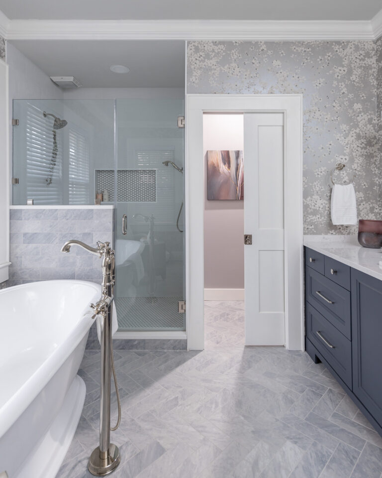 grey floor and shower tile, white pocket door, blue vanity, master bath